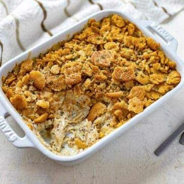 baked casserole in a white oblong dish with one serving removed and spoons on the side