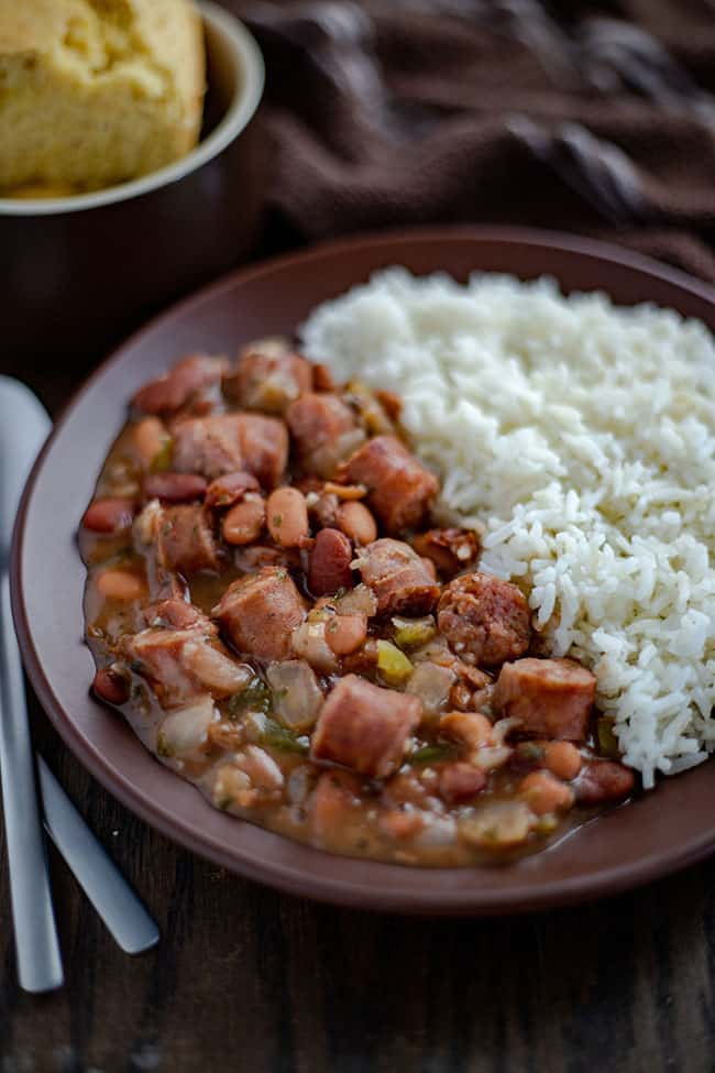 red beans and sausage next to rice on brown plate with cornbread on the side