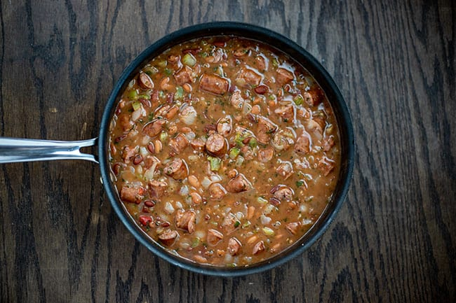 browned sausage with frozen chopped vegetables and beans in pan