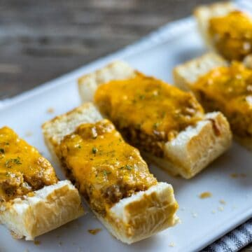 cheesy stuffed french bread slices on white plate