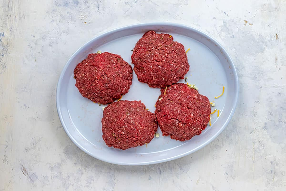 four uncooked stuffed patties