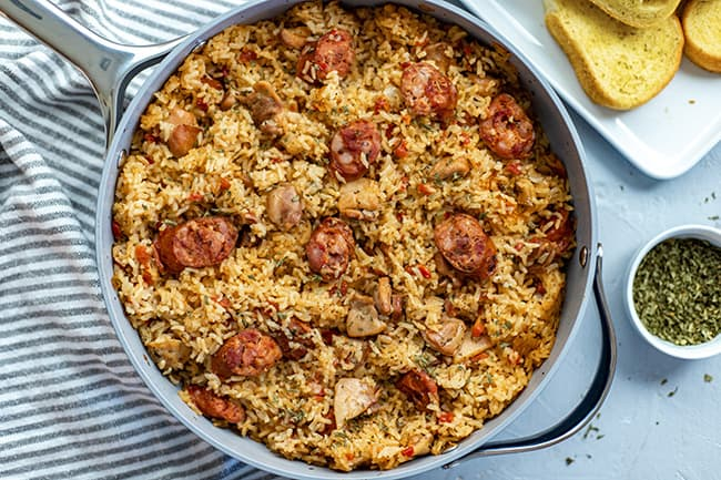 New Orleans Jambalaya in skillet with buttered french bread on side