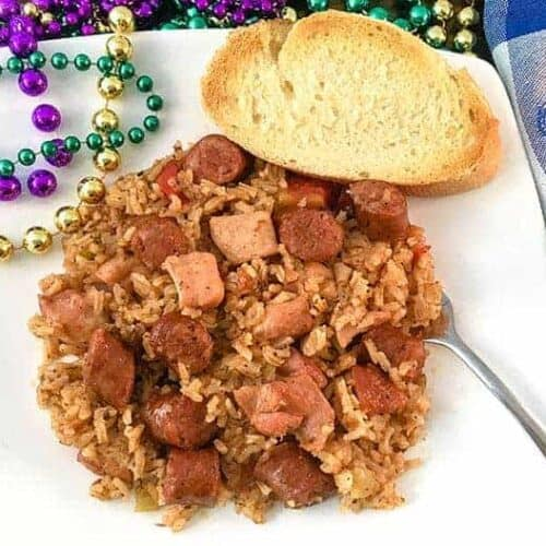 chicken and sausage jambalaya on white plate with mardi gras beads on the side