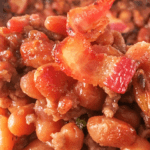 baked beans in casserole dish with bacon on top