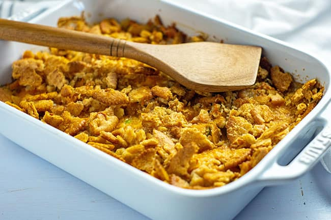 baked southern cabbage casserole in a white staub rectangular baking dish with a wooden spoon