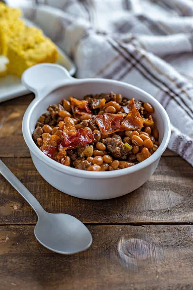 baked beans in white bowl with cornbread in background