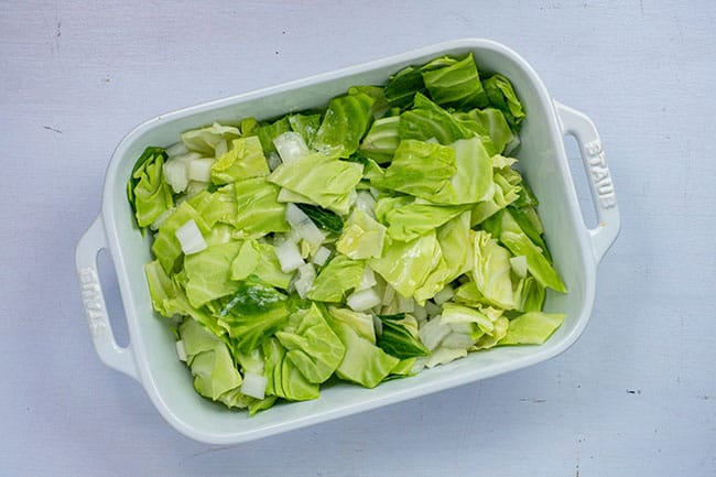 chopped cabbage and onion in white staub casserole dish
