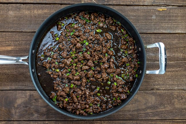 cooked ground beef and seasonings in pan