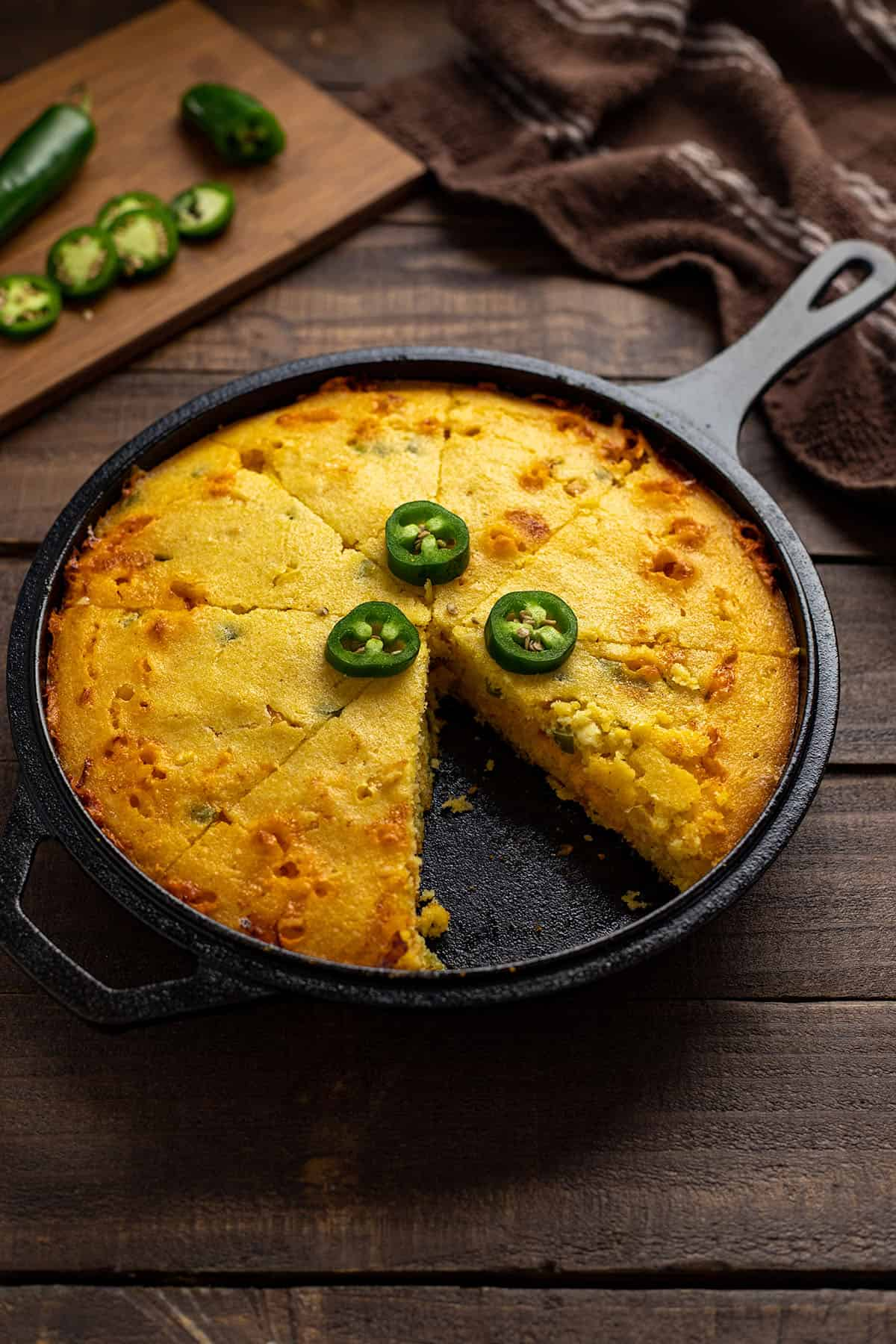 baked cornbread with 3 jalapeno slices on top in cast iron skillet with one slice removed