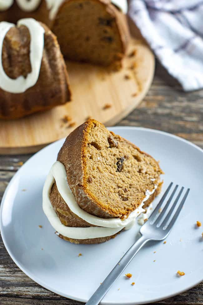 slice of pumpkin spice bundt cake on a white dessert plate with silver fork and remaining bundt cake in the background