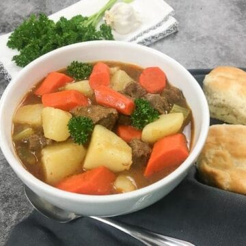 Beef and Vegetable Stew in White Bowl with two biscuits on the side