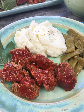 baked meatloaf on blue plate with mashed potatoes and green beans