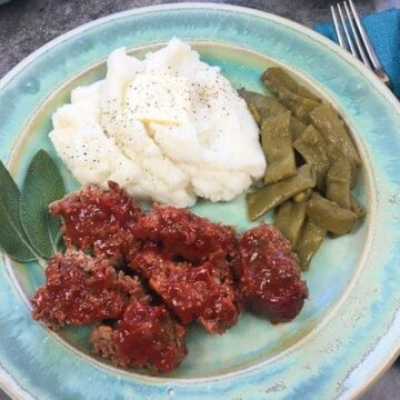 meatloaf on a blue plate with mashed potatoes and green beans