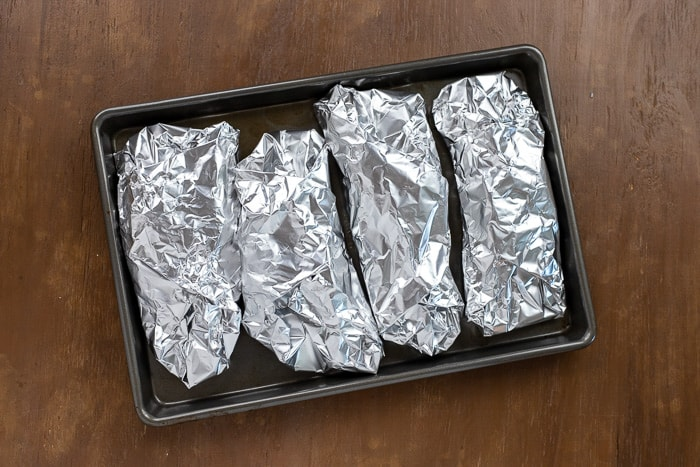 foil wrapped chicken breasts on baking pan