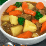 vegetable beef stew in white bowl with spoon