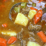 vegetable beef stew in black pot with ladle