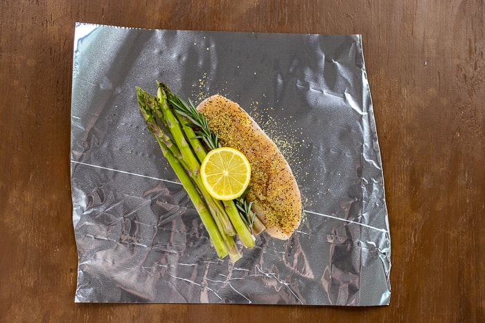 uncooked seasoned chicken breast with asparagus rosemary and lemon slice on sheet of foil