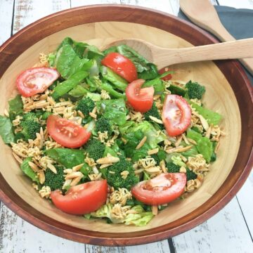 romaine lettuce, tomatoes, broccoli, toasted almond slivers and Ramon noodle pieces in a wooden salad bowl with wooden spoon