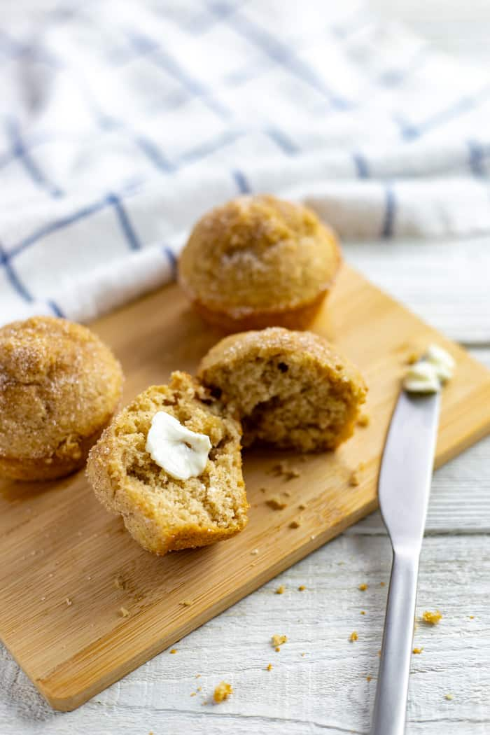 baked cinnamon applesauce bisquick muffins on a wooden cutting board with one split open and slathered with butter