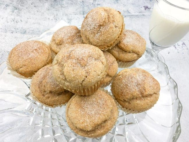cinnamon applesauce muffins on glass cake plate with glass of milk