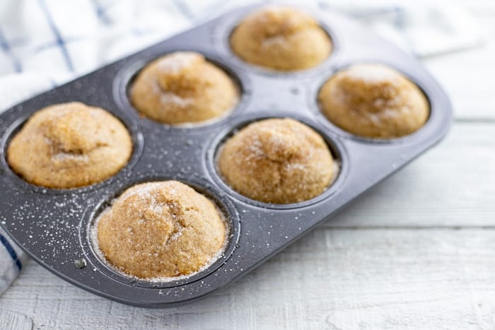 baked applesauce muffins in muffin tin with cinnamon sugar topping