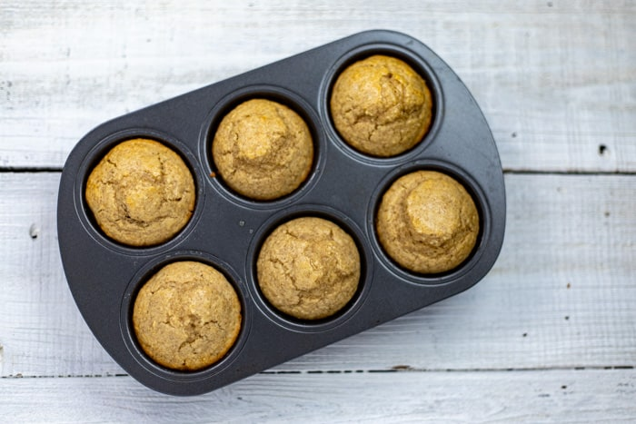 baked cinnamon applesauce muffins in the baking tin without sugar topping