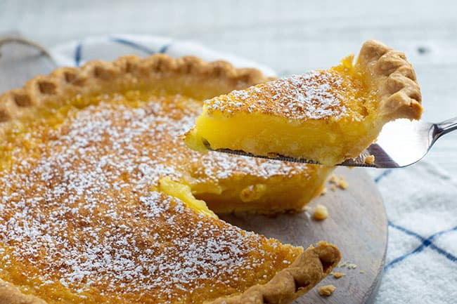 lemon chess pie with a slice taken out on a pie server