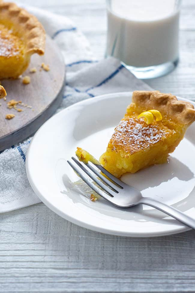 slice of lemon chess pie on a white plate with a silver fork and a twist of lemon zest