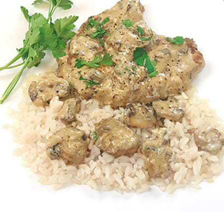 cooked chop covered with mushroom gravy on rice