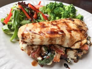 baked chicken breast on white plate with mixed vegetables
