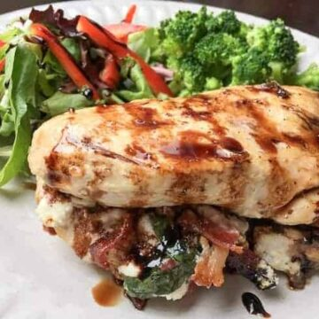 stuffed chicken breasts on plate with side salad