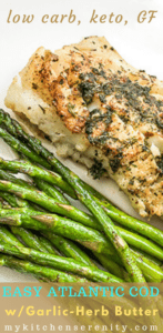 baked cod with garlic herb butter on top next to asparagus spears on white plate