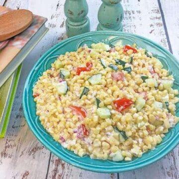 creamy cold corn salad inside teal blue bowl