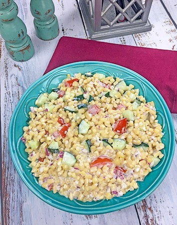 creamy cold corn salad in blue serving bowl with red napkin