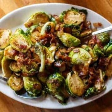 roasted brussels sprouts with bacon in white bowl with two forks