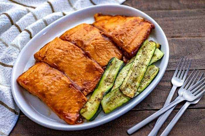 Four BBQ Grilled Salmon Fillets on white platter with grilled zucchini slices on the side