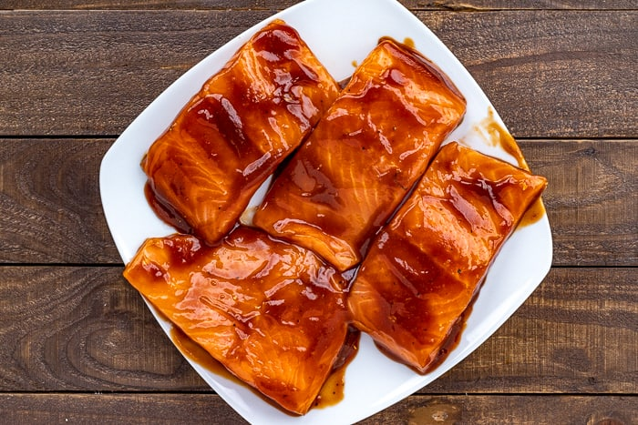 BBQ marinade on 4 uncooked salmon fillets on white square plate