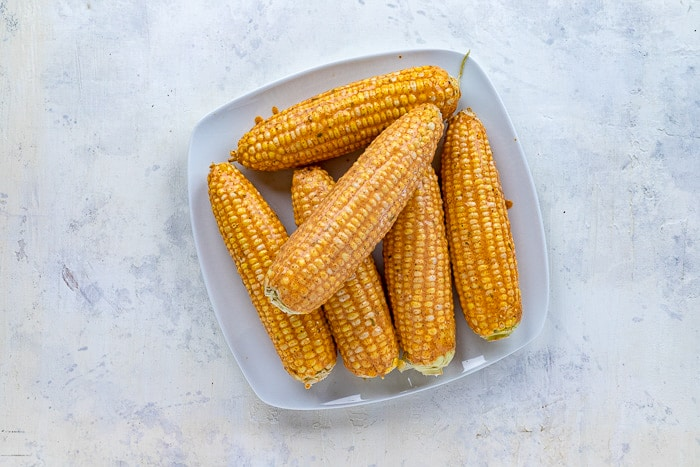 uncooked corn on cob with sauce applied