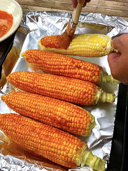 applying sauce to corn on the cob with a brush