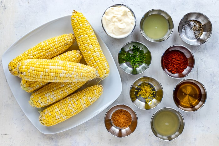 uncooked and shucked corn on cob with ingredients measured out in individual bowls laid out on countertop