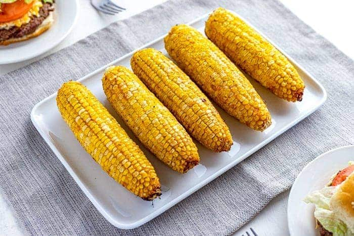 five ears of grilled corn on white rectangle platter