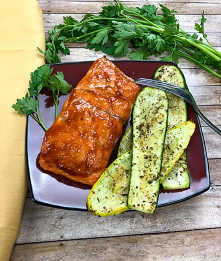 cooked salmon with grilled zucchini on plate