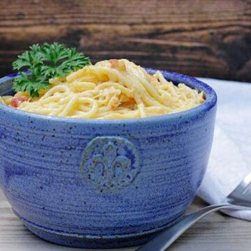 rotel chicken spaghetti in blue bowl with white napkin and fork