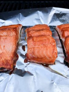 three salmon filets grilling on tinfoil