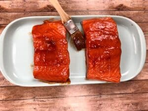 brush being used to put bbq sauce on salmon filets