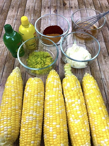 uncooked and shucked corn on the cob with recipe ingredients in bowls