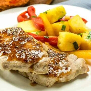 sweet & sour pork chops on white plate with bell pepper slices and pineapple chunks
