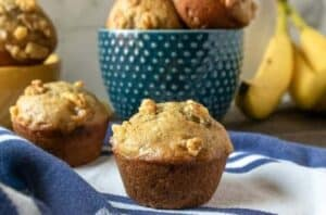 banana nut muffin on plate with bowl of muffins and fresh bananas in background