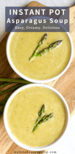 two white bowls filled with creamy asparagus soup and asparagus spears as garnish