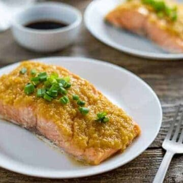 miso salmon fillet on white plate with green onion slices on top
